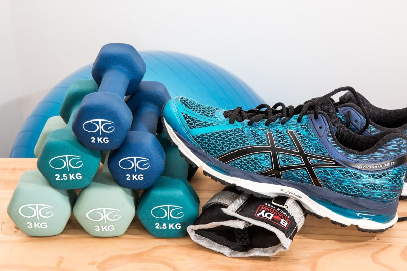 A photo of blue running shoes leaning up against blue weights.