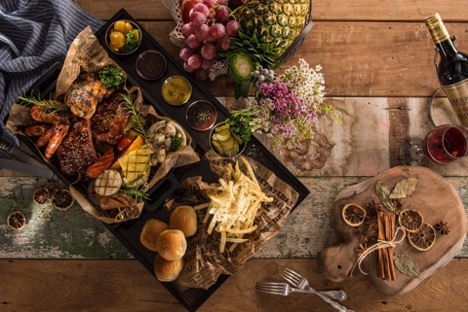 A delicious platter of meat, bread and cheese with condiments, fruits and wine