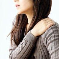 肩が痛いんで思わず手をあてる女性イメージ