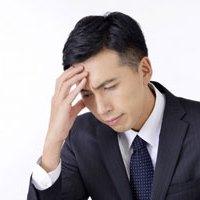 頭痛で頭を抱える男性イメージ