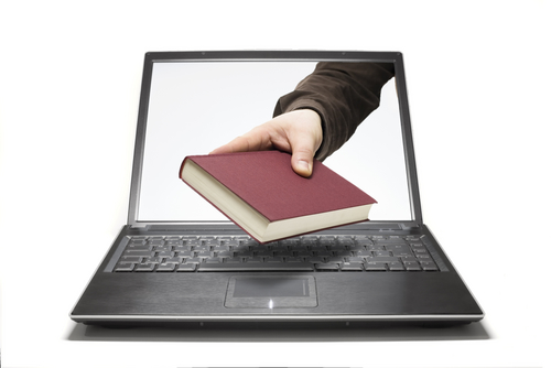 Image of a person handing a book through a laptop screen