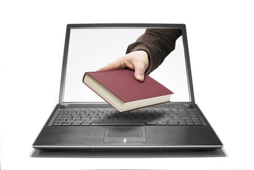 Image of a person handing a book through a laptop screen
