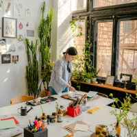 craftswoman working with drafts at table with stationery in workshop