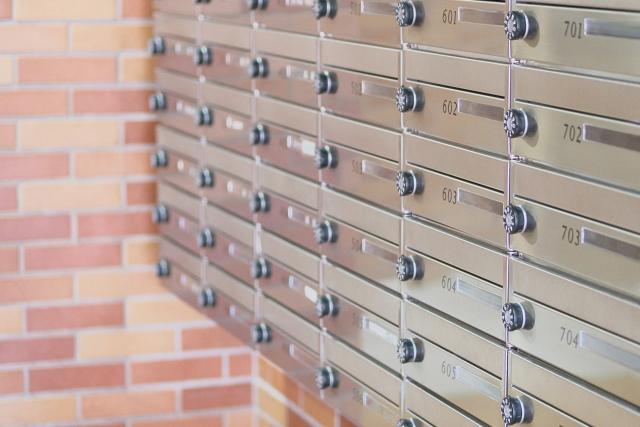 郵便配達員がポストに郵便物を入れる