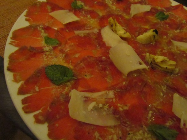 close up of carpaccio di manzo, con scaglie di parmigiano e carciofini