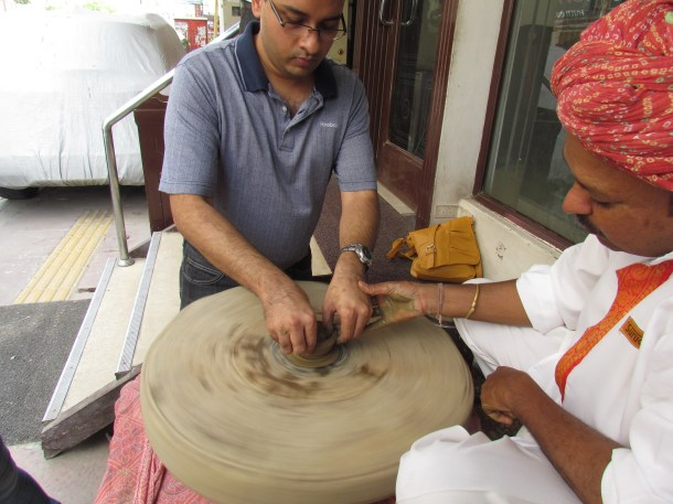 The pottery guy helping customer making his own potteryon the wheel