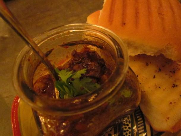 pickled goan pork sausages served in small glass jar