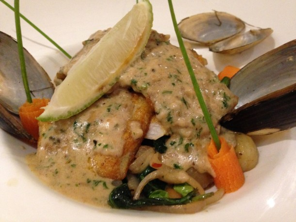 Pan Grilled fresh water bhetki with a French Mussel cream sauce on a bed of lemon, shallot, peas, spinach & potatoes