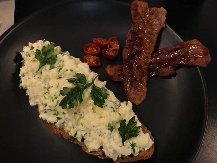 Scrambled egg with garlic, parsley, Parmesan on toast, thyme roasted tomatoes and coffee glazed pork bacon