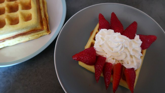 Stack of keto waffles and one topped with strawberries and cream