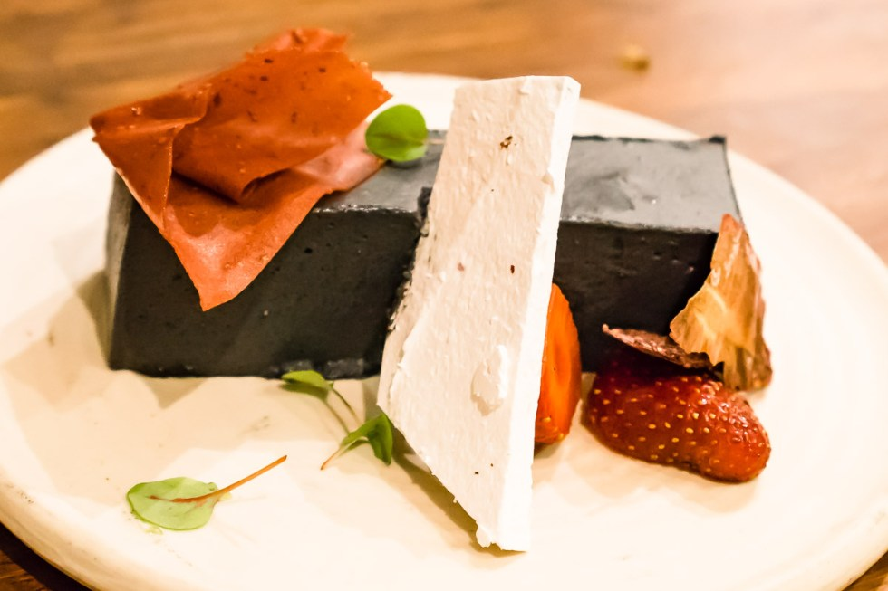 This is a photograph of dessert, a Black sesame bavaro is, strawberries, pink peppercorn meringue, sorrel at A.Baker