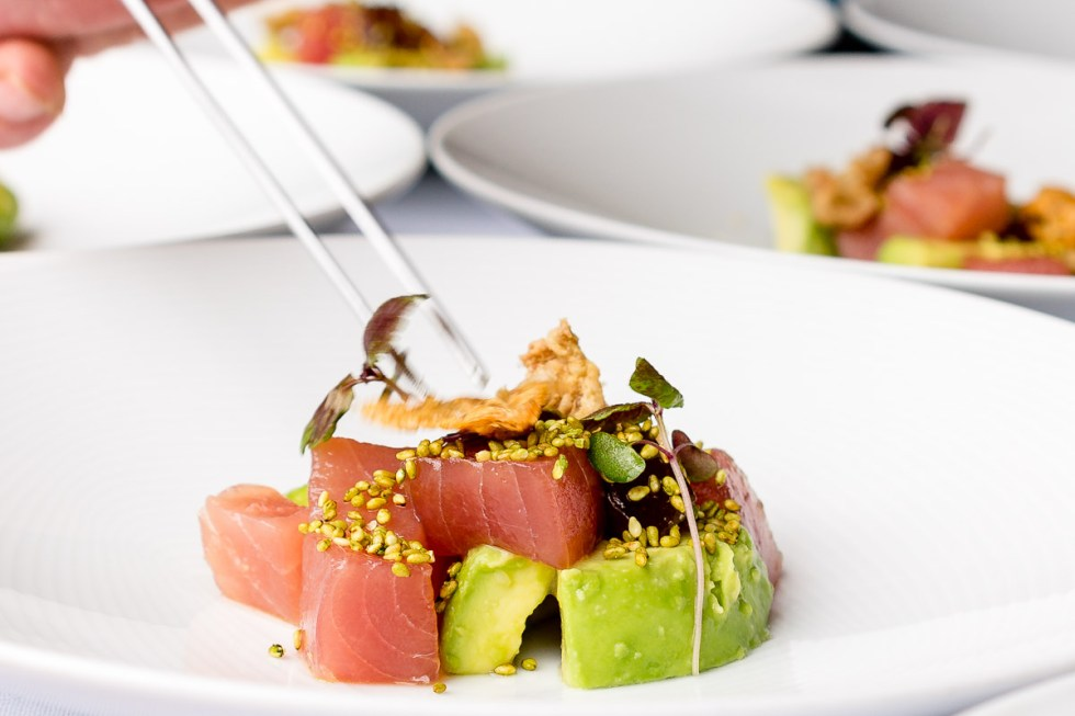 This is a photograph of the final plating up of Yellow fin tuna, avocado, chicken skin crackling and wasabi jelly with wasabi sesame seeds