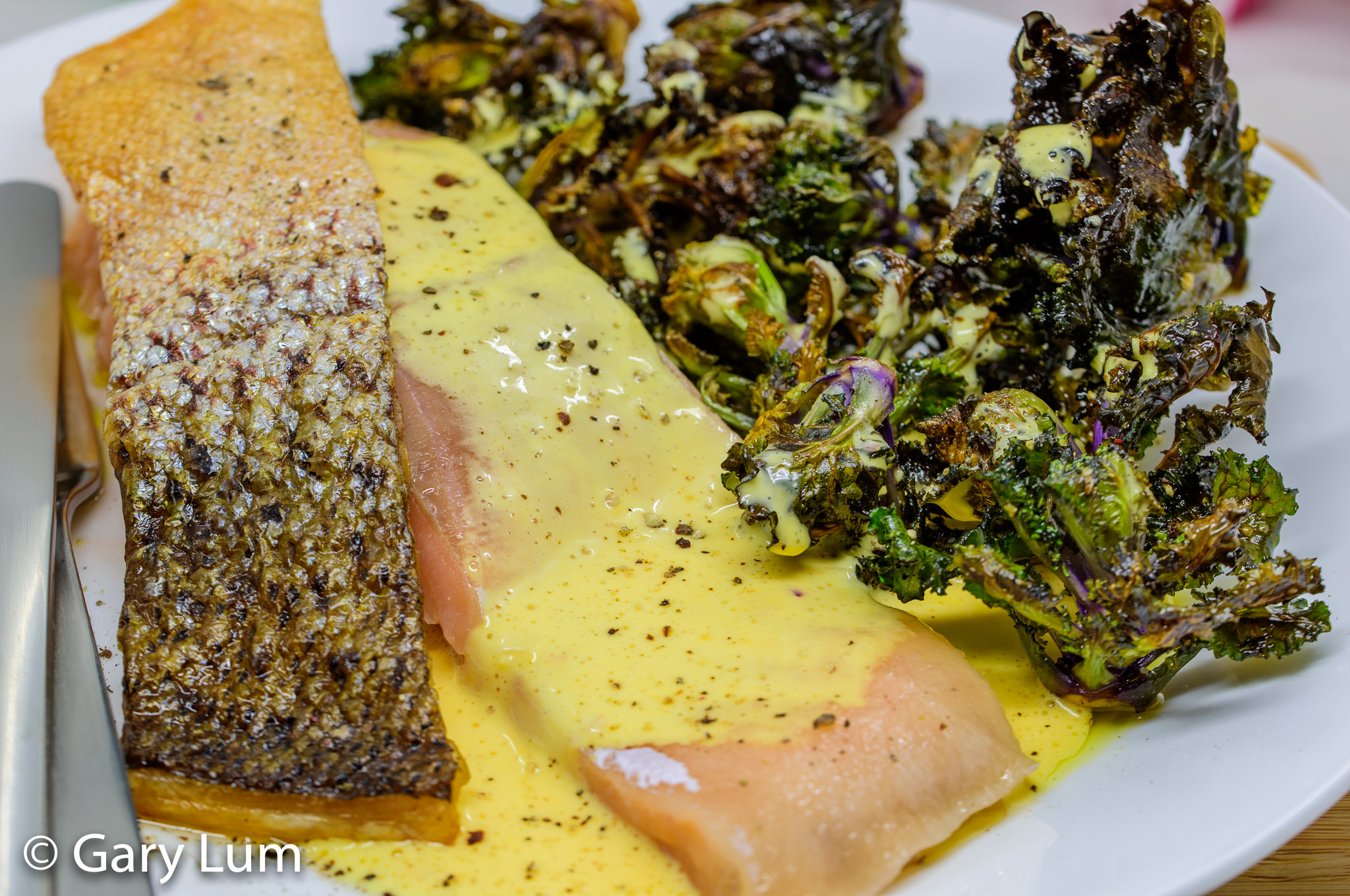 Sous vide salmon, spicy hollandaise sauce, and kale sprouts