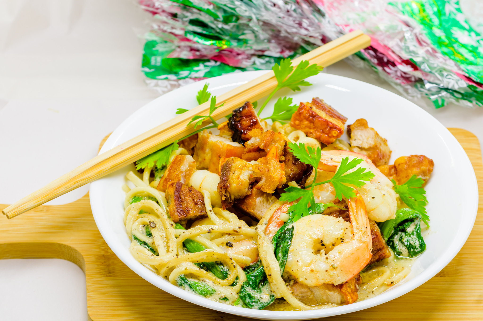 Garlic Udon noodles, coconut cream, pork belly, prawns, and choy sum