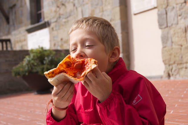 Yves mangia un buon pezzo di pizza davanti al palazzo comunale