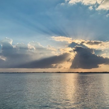 The sun rays break through the clouds and paint beautiful beams into the morning sky