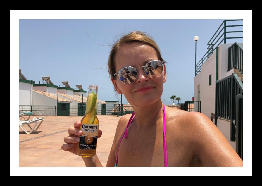 Yvonne holder en liten Corona-flaske