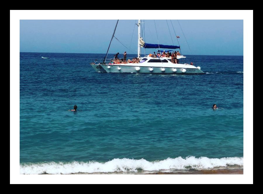 Strand og seilbåt ved Tauro
