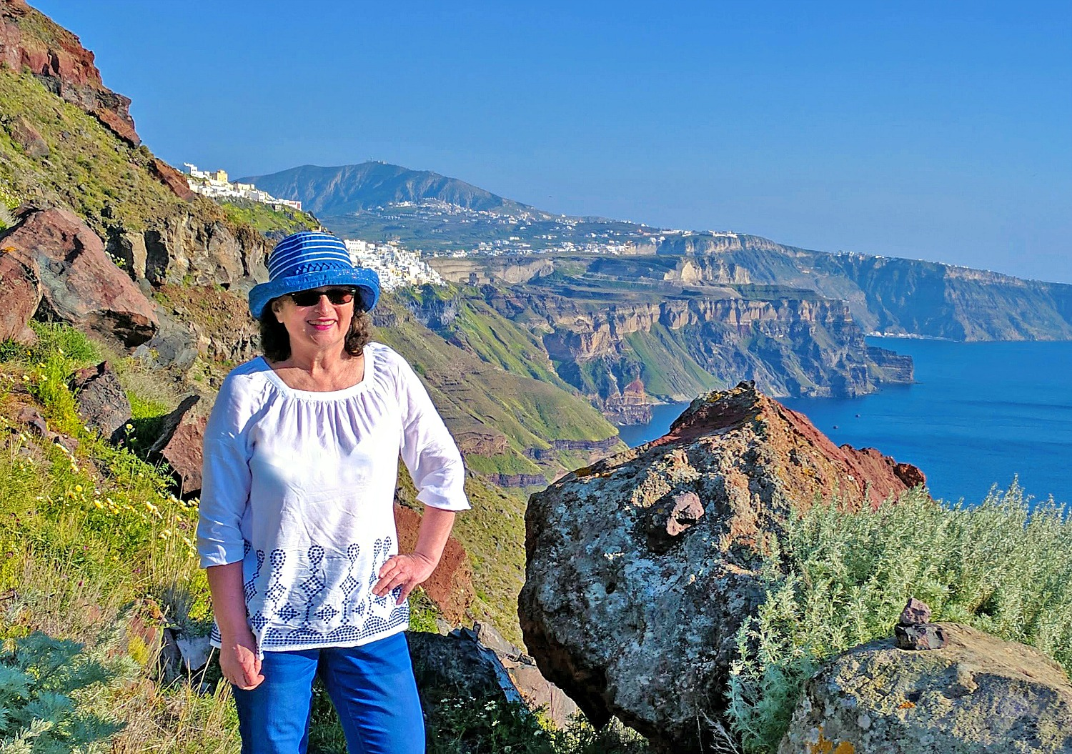 Lady smiling along hiking trail in Santorini Greece.