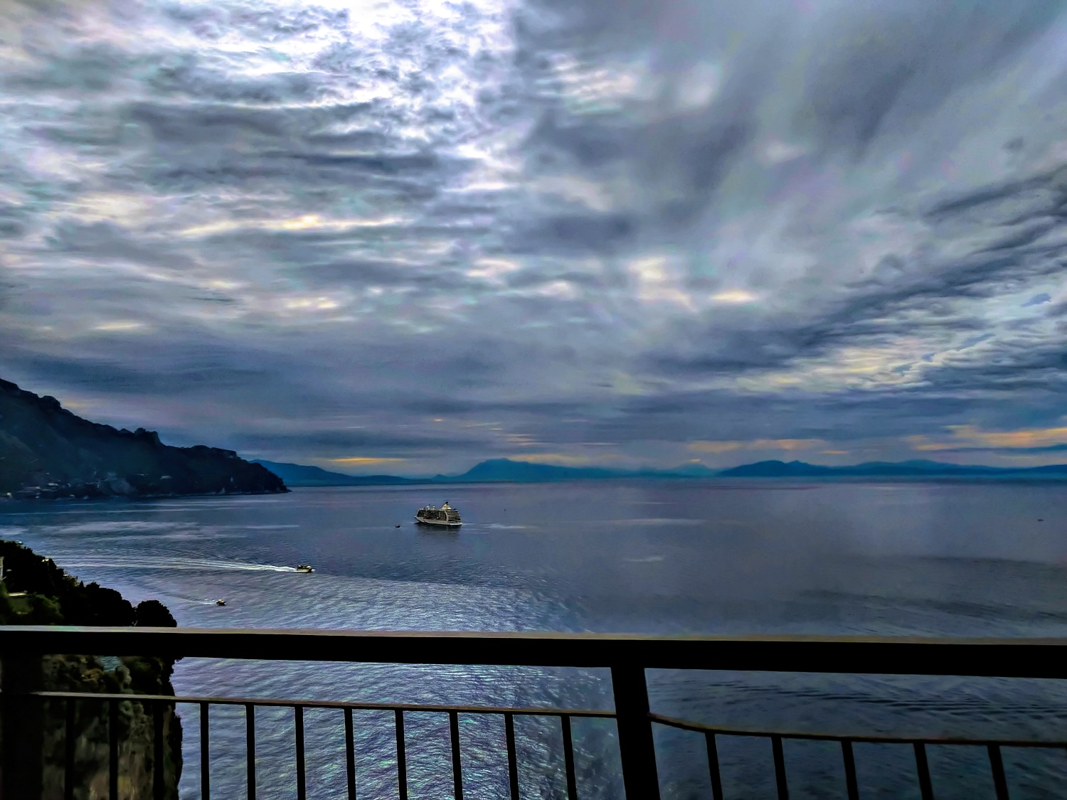 An early morning drive along the Amalfi Coast with a ship in a distance view.