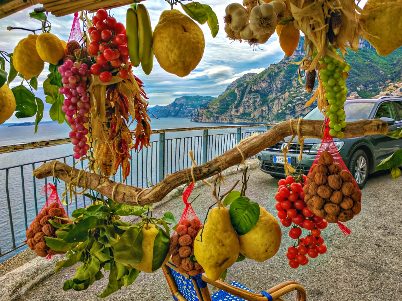 Views of the Amalfi Coast framed with hanging fruit.