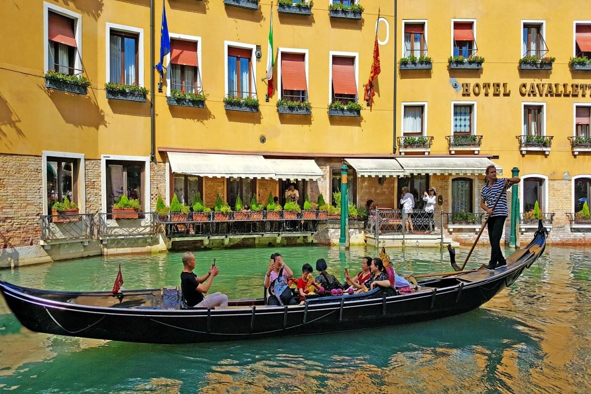 Venecijos pasivažinėjimas gondolomis priešais geltonai nudažytą viešbutį.