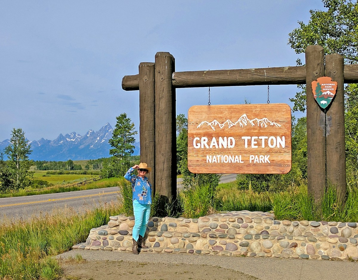 Grand Teton itinerary. A lady posing at the Grand Teton National Park welcome sign.