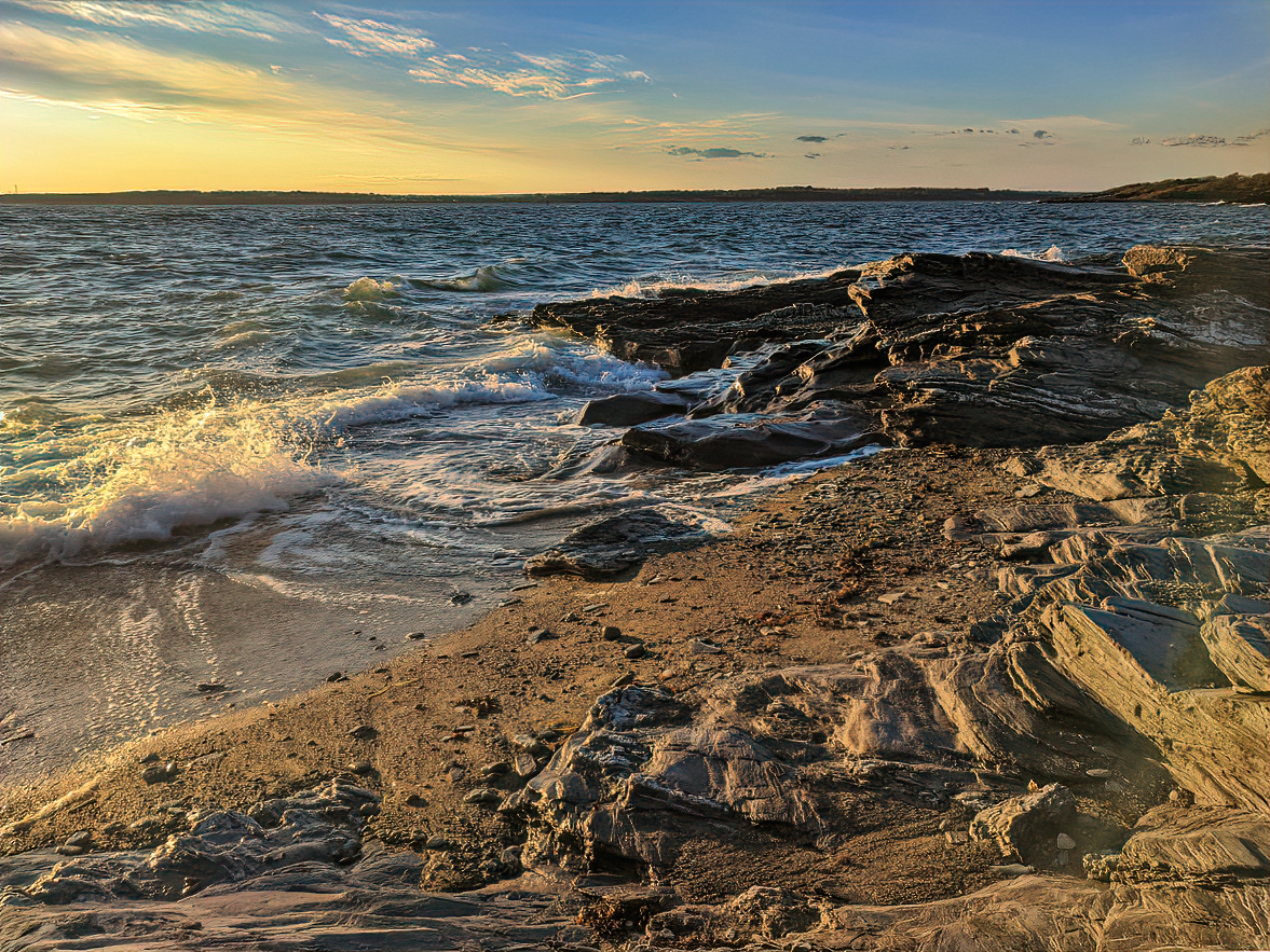 Rocky shoreline at sunset at Newport, Rhode Island.
