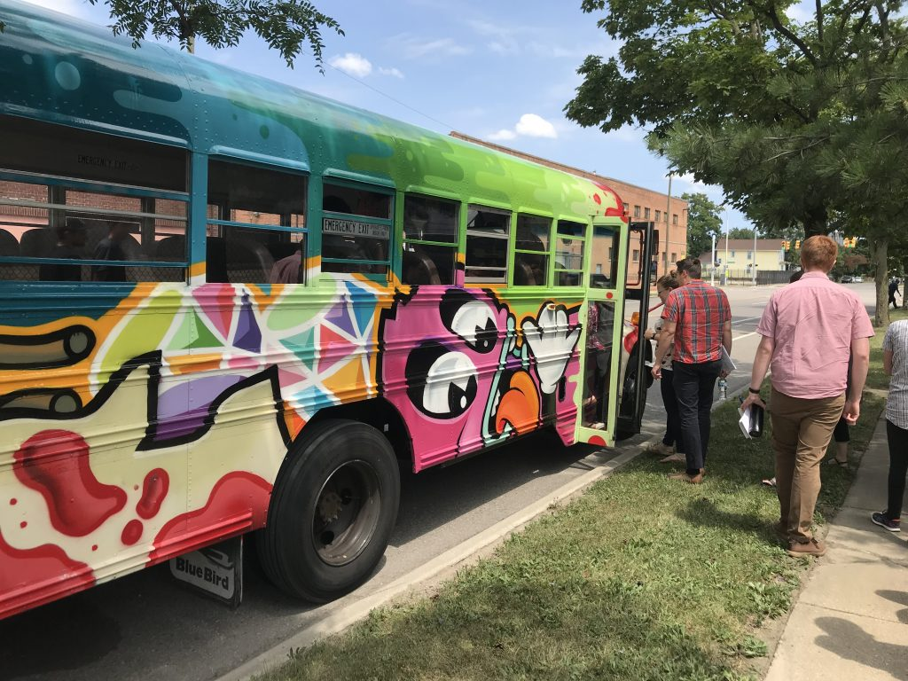 Photo of the learning exchange partners boarding the colorful Detroit Bus Company's bus for a the tour.