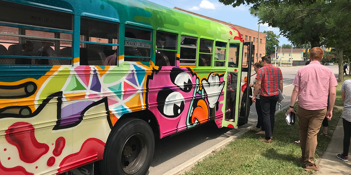 Partners getting onto one of the Detroit Bus Company's buses to tour vacant land reuse options in Detroit. (1200x600)