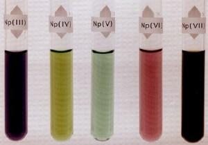 Oxidační stavy neptunia a jejich zbarvení. Od Los Alamos National Lab. (http://www.chemie-master.de/pse/pse.php?modul=Np) [Public domain], prostřednictvím Wikimedia Commons