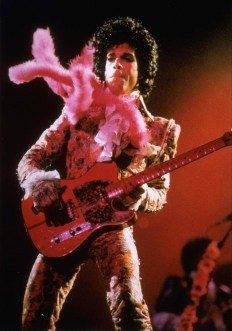 Prince playing guitar in concert