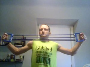 Zachary Fenell working out using his chest expander.