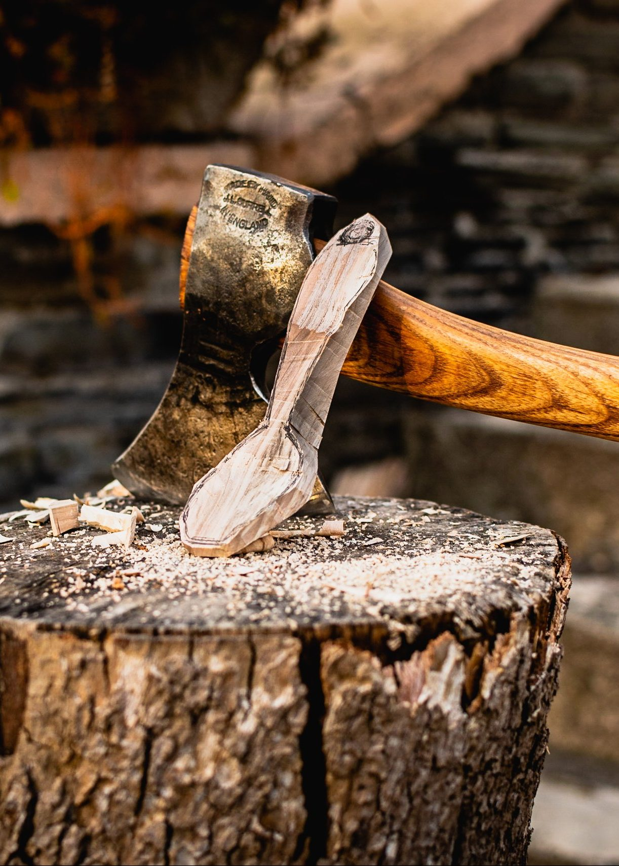 partly-carved wooden spoon resting on an axe