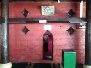 Pintu masjid dari luar. terlihat seorang pengunjung ada di dalam. Tinggi pintu hanya sepundak orang dewasa.