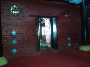 Pintu masjid dari dalam dengan ornamen keramik di samping pintu.