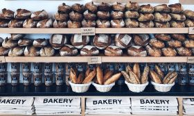 image of Zak The Baker retail display of sourdough breads, baguettes, granola, and bags.