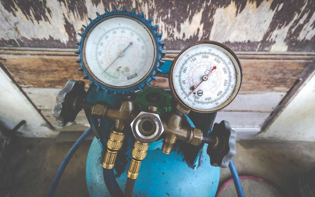 Manifold gauge kit placed on refrigerant tank