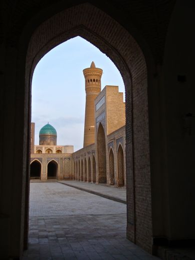 """Bukhara has a gritty, inhabited feel to it: people walk freely through occasionally crumbling medieval monuments, groceries in hand, while shop keepers hawk wares from under the domes of ancient bazaars. With no tourists about in mid-winter, we were able to wander undistracted through the madrases, mausoleums, and mosques. Here, the Po-i Kaylan (""""Foot of the Great"""") complex, showing the minaret of the Kaylan mosque and the turquoise dome of the Mir-i Arab Madrasah."""