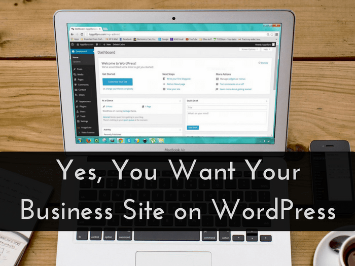 """Macbook laptop sitting on a brown table with WordPress dashboard open next to a cup of coffee, with the title """"Yes, You Want Your Business Site on WordPress"""" across the lower center of the photo"""