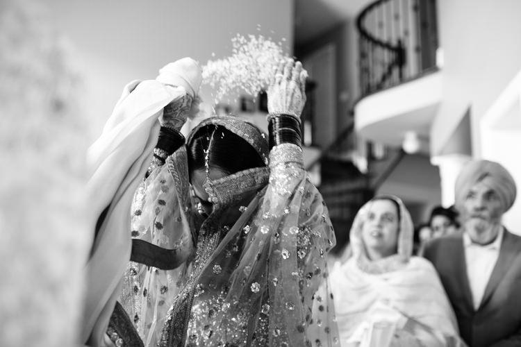 Bride throwing rice at Indian sikh wedding doli