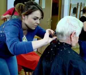 Katarzyna Kapela, uczestniczka Hufca Pracy z Oświęcimia podczas podcinania włosów seniorce | fot. Ewelina Sikora