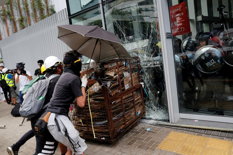 Protesters try to break into the Legislative Council building where riot police are seen, during the anniversary of Hong Kong's handover to China in Hong Kong