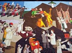 detal muralu, przedstawia m. in. cios młotem uśmiercający krowę