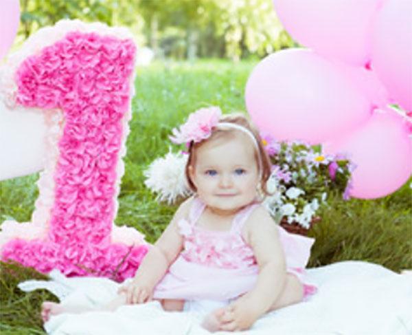 Девочка в розовом платьице, с таким же ободком на голове. Рядом розовые шарики и розовая объемная единица