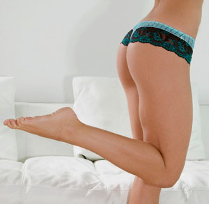 Low section view of a woman, standing on one leg in front of a couch