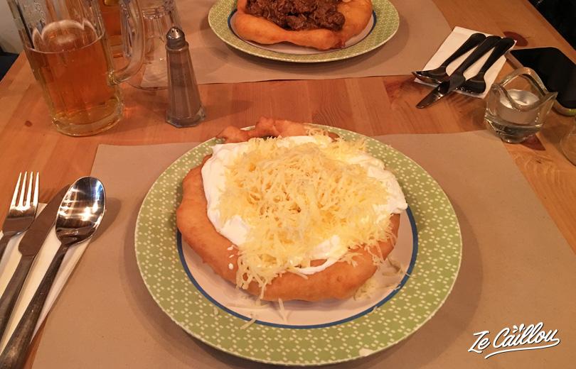 Découvrez les langos hongrois, une galette de pain avec de la crème et du fromage.