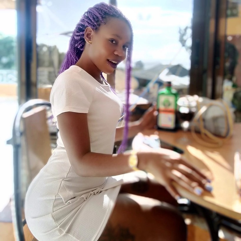 Chebet Pinky Banda seated on a table in a white dress