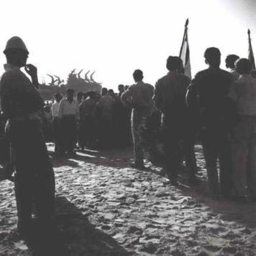 כנס זיכרון לאלטלנה ב-1949. ברקע השלד השרוף של האוניה.