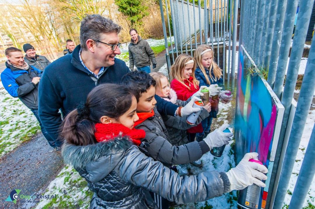 (Wijk)wethouder Roy Luca verzorgt samen met buurkinderen van de graffitiworkshop de 'finishing touch'. Samen spuiten zij het lint door.